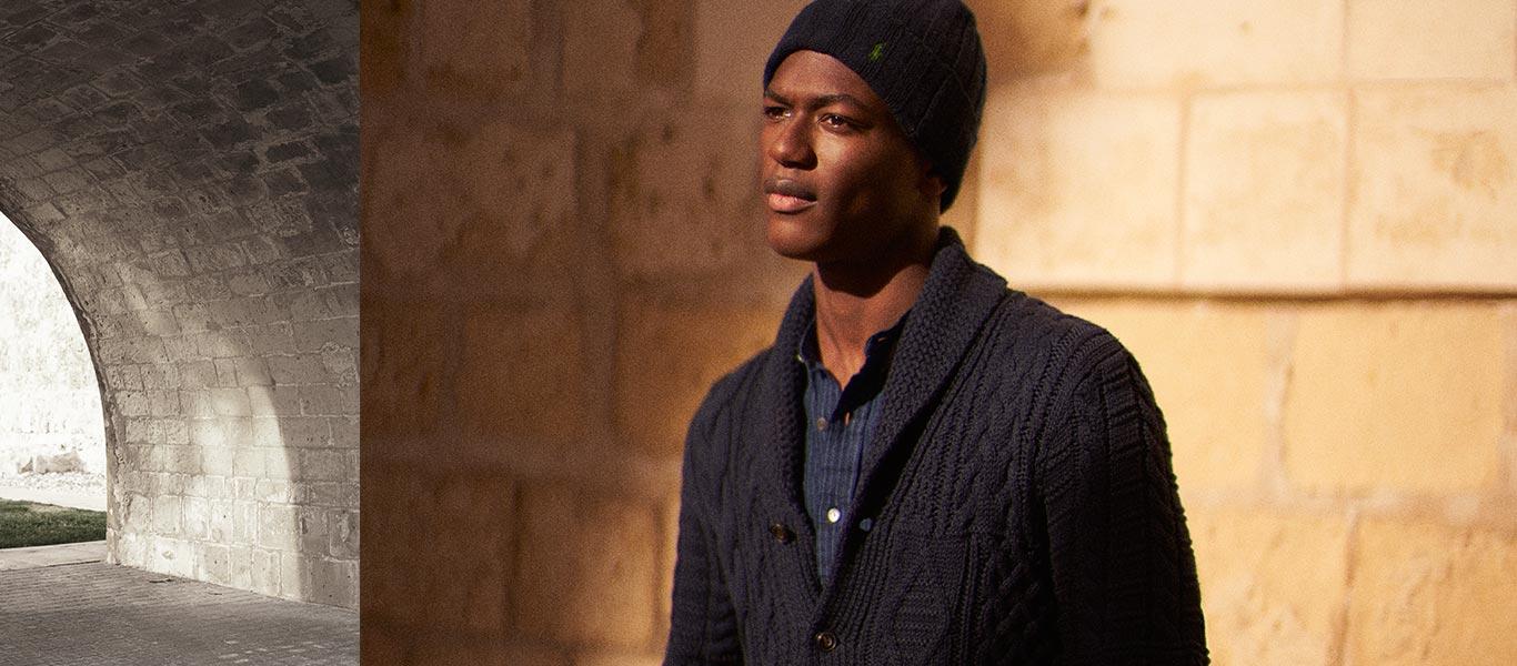 Man in navy shawl-collar cardigan & knit hat