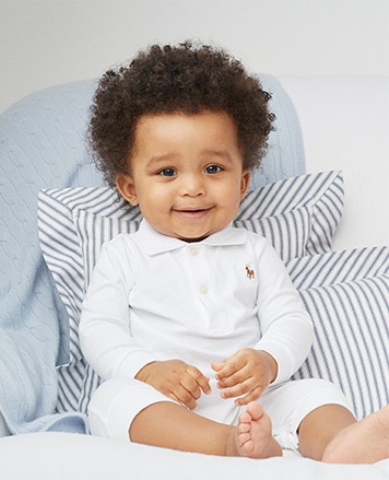 Baby boy wears white shortall with a signature embroidered pony at the chest.