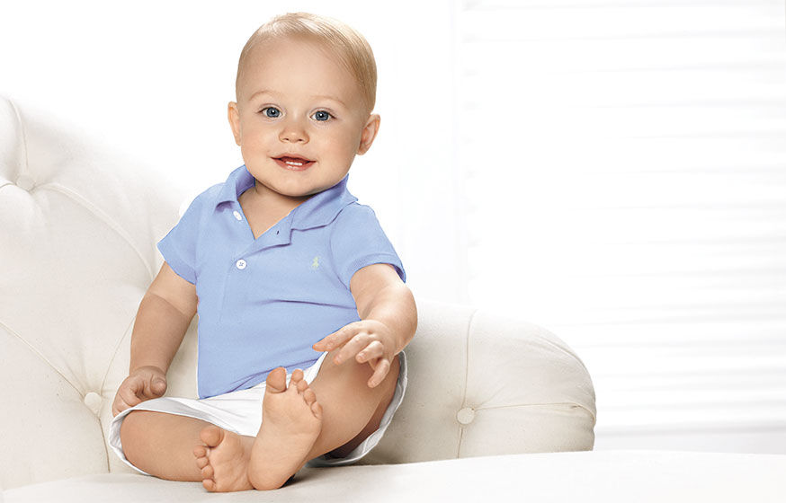 Baby in light blue Polo shirt & white short sits in white tufted armchair
