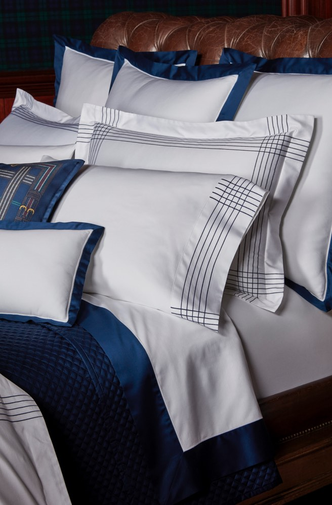 Bed appointed with white & blue sateen sheeting & shams