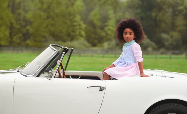 Girl wears striped fun shirtdress and sits on back of car.