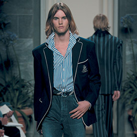 Male model walking down runway in blue sport coat paired with denim