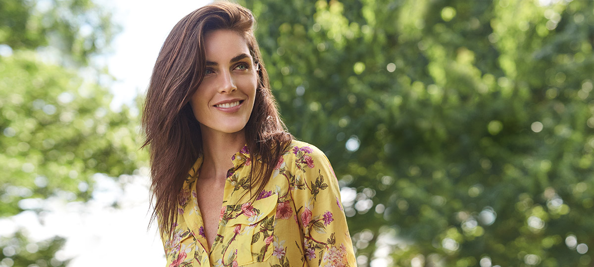 Model outside on sunny day in yellow blouse with pink floral print
