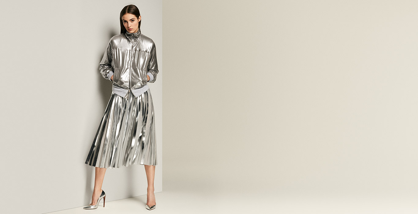 Woman in metallic silver bomber jacket & pleated skirt
