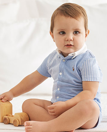 Baby boy wears knit oxford fun coverall.
