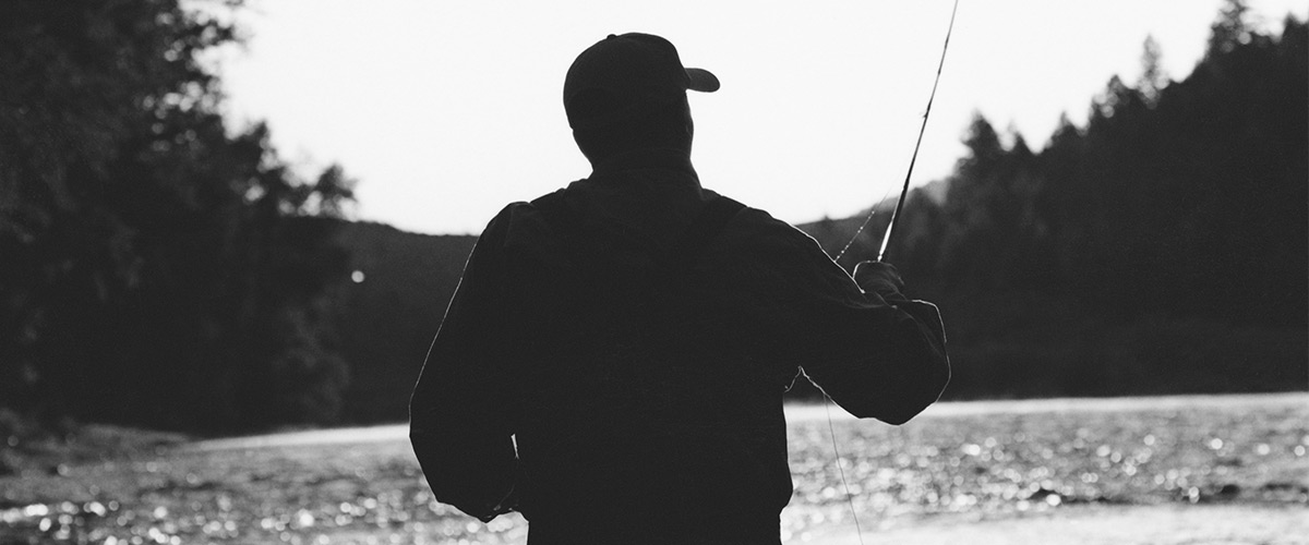 Silhouette of man fly-fishing