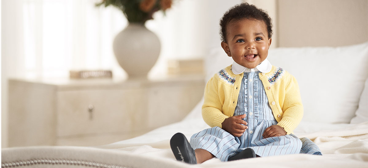 Baby girl wears blue striped shirtdress and yellow cardigan.