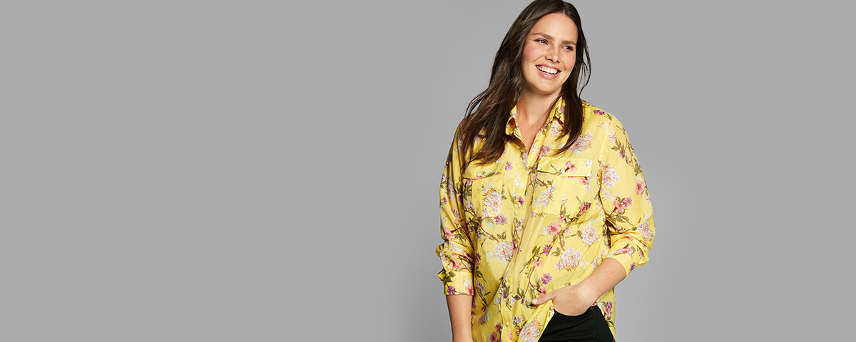 Plus-size model in yellow blouse with pink floral print