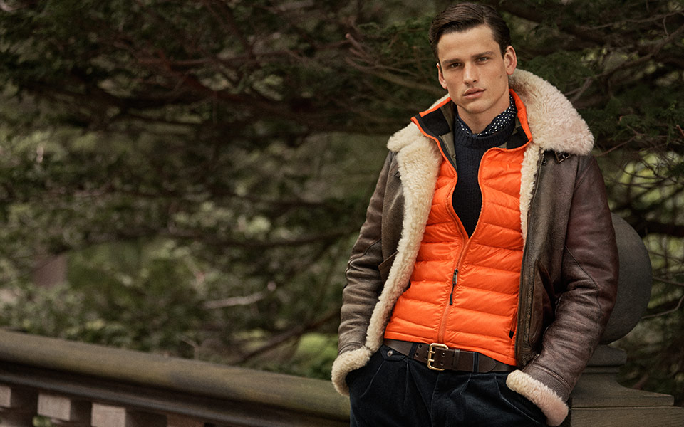 Man in shearling brown leather jacket layered over orange vest