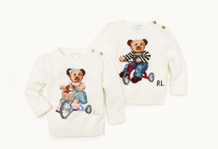 Cream-toned sweaters, each with knit image of Polo bear on tricycle