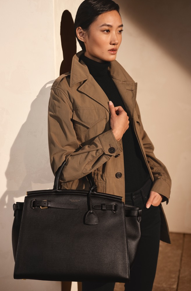 Woman carrying large black leather handbag with belt accents