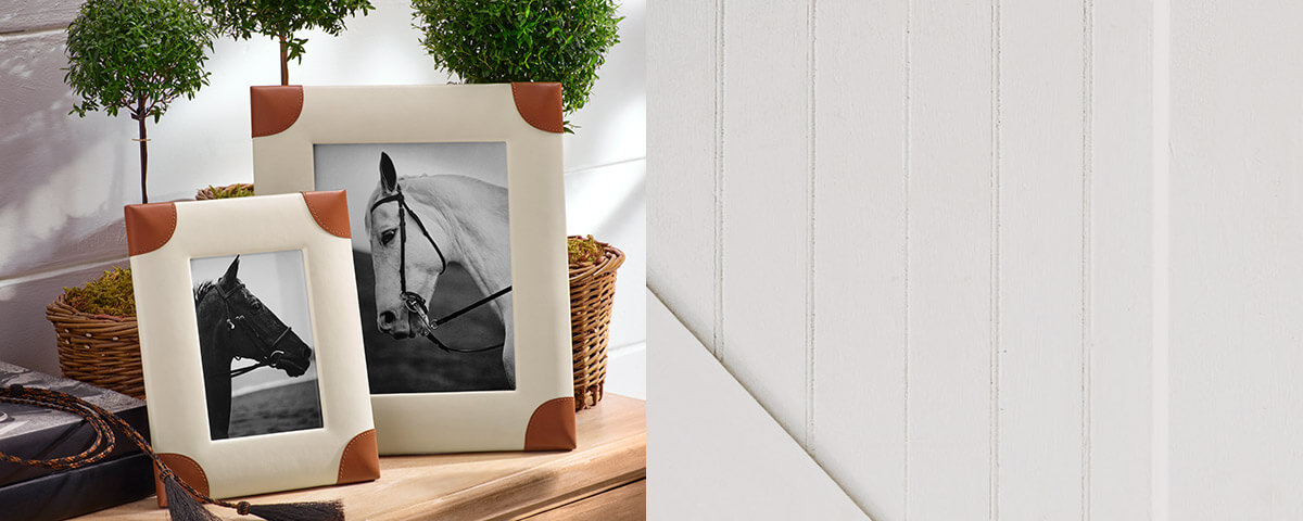 Off-white pictures frames with leather trim at corners