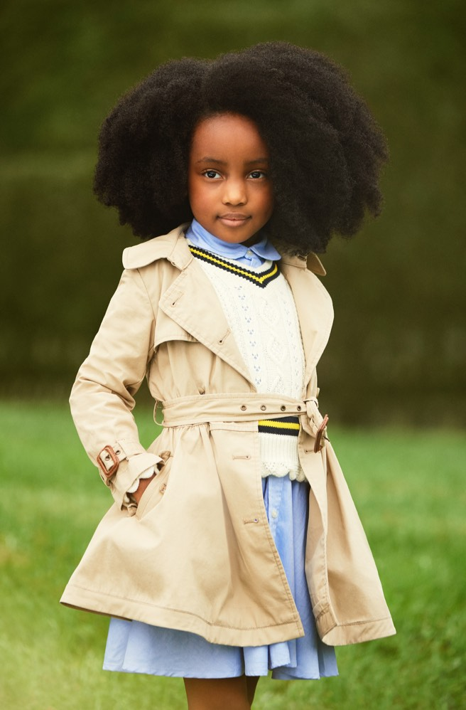 Girl wears trench coat over sweater and shirtdress.
