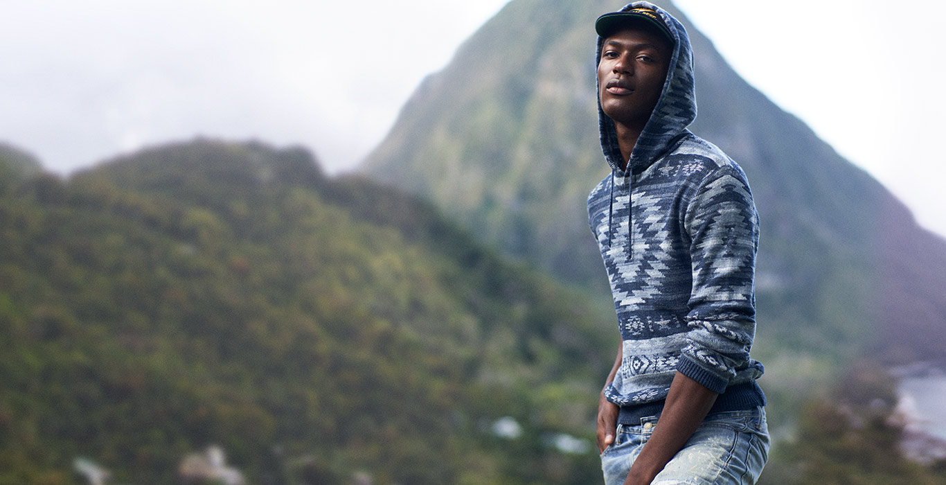 Model outdoors in hooded sweater with Southwestern-inspired indigo motifs