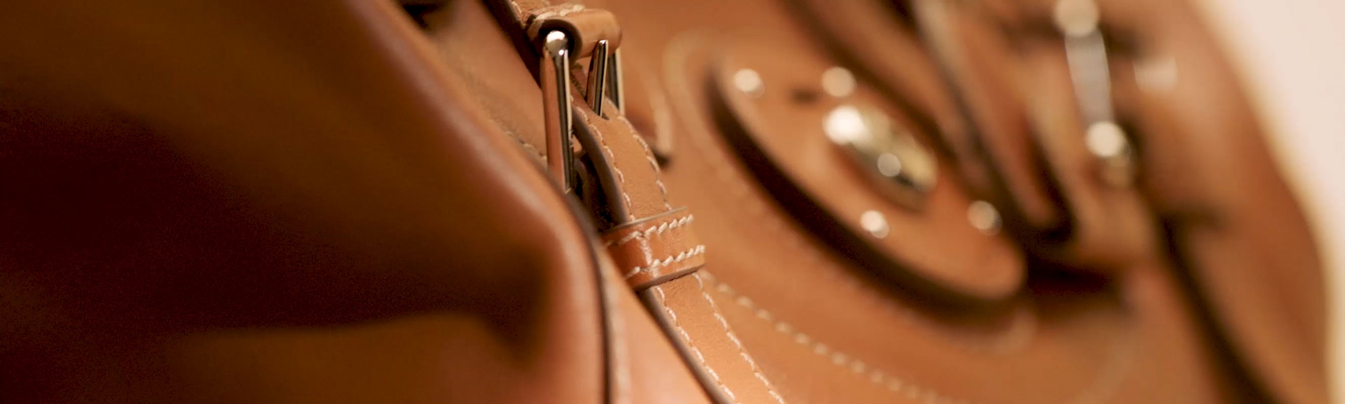 Close-up of 'Ralph Lauren'–embossed Ricky lock on brown leather bag
