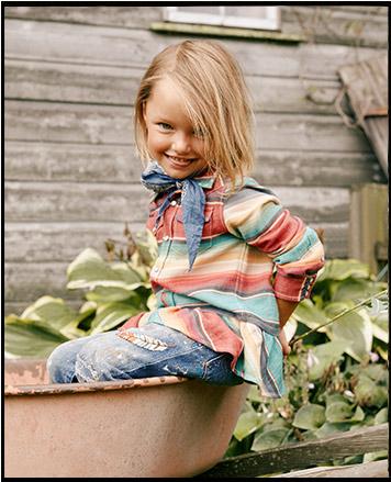 Girl wears serape Western top.