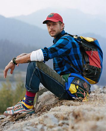 Man sitting along trail in blue buffalo check button-down