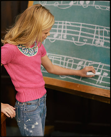 Girl wears pink short-sleeve sweater and writes on chalkboard.