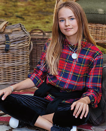 Girl wears red plaid button-down shirt and velvet leggings.