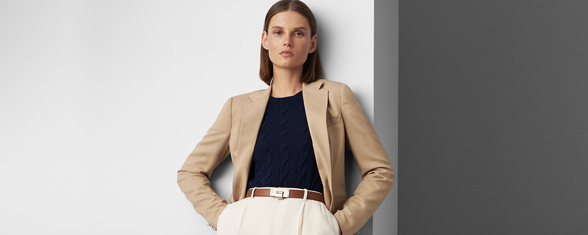 d5f76d0f328 Ralph Lauren Collection. Woman in sleek tan blazer, slim cable sweater &  white trousers