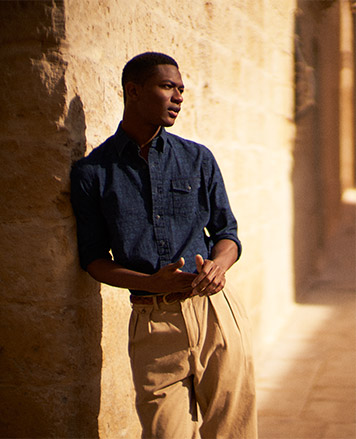 Model wears navy button-down shirt and chinos.