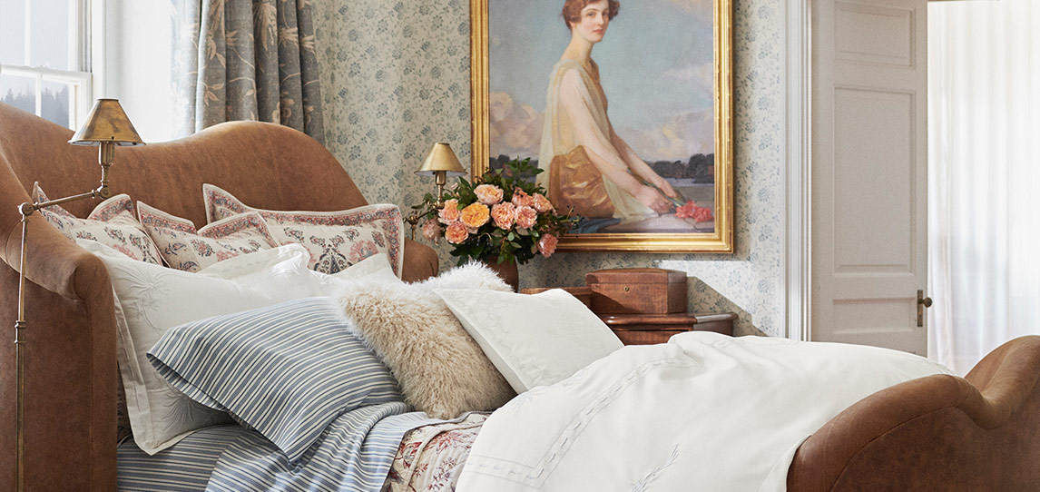 Bed with wooden frame and sheeting with artful stripes & florals