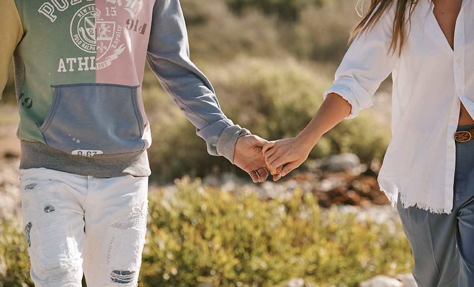 Close-up of models holding hands in Polo attire.