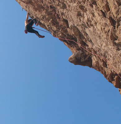 Photograph of Chris Sharma scaling the side of a cliff