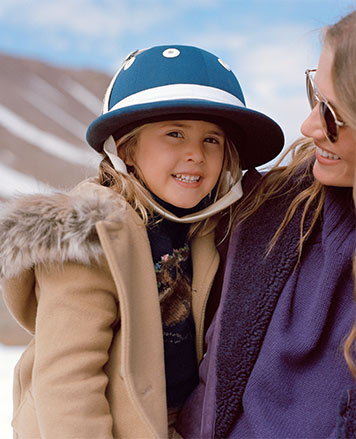 Girl wears tan coat with faux-fur collar and riding helmet.