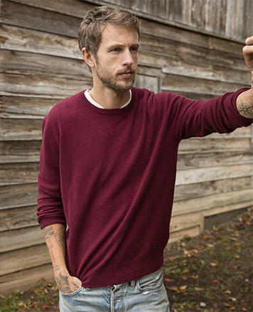 Man in wine red crewneck sweater & jeans