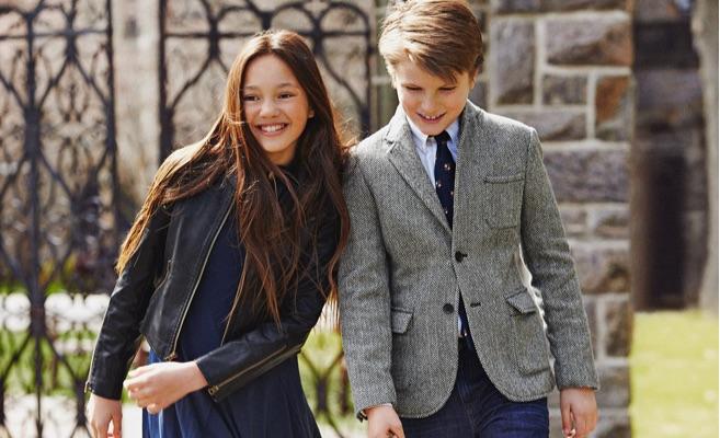 Girl wears black leather jacket over navy dress; boy wears herringbone blazer and jeans.