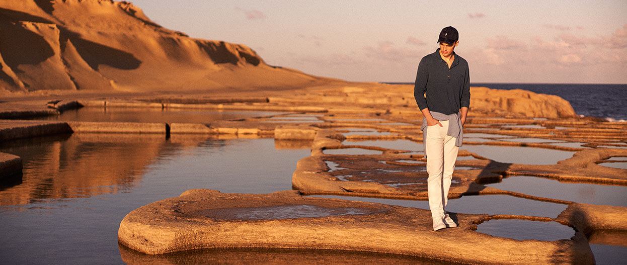 Man on sand bar in white jeans & navy long-sleeve shirt