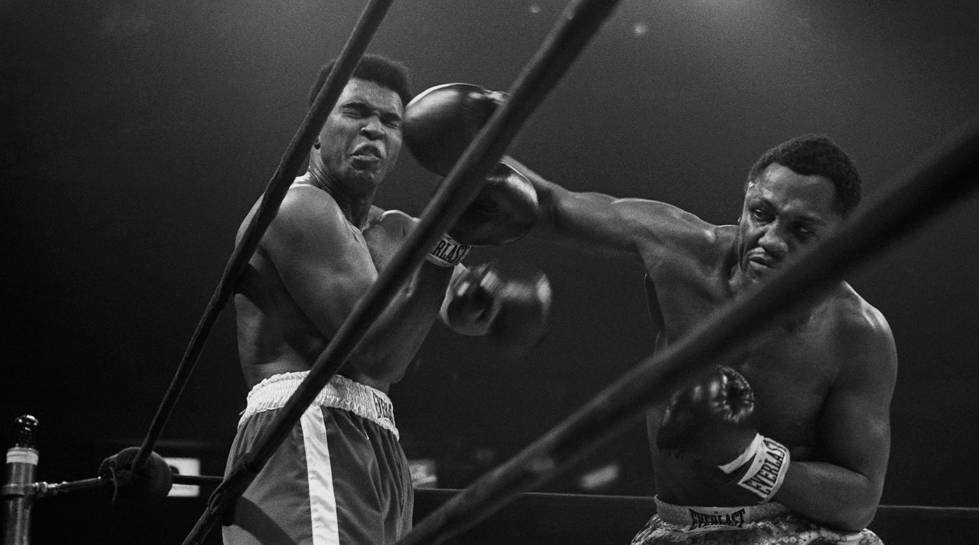 Heavyweight champion Joe Frazier delivers a Herculean blow against Muhammad Ali in the Fight of the Century