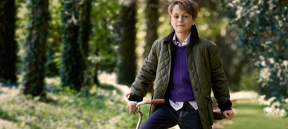 Boy on bike wears green quilted jacket over purple cable-knit sweater and jeans.