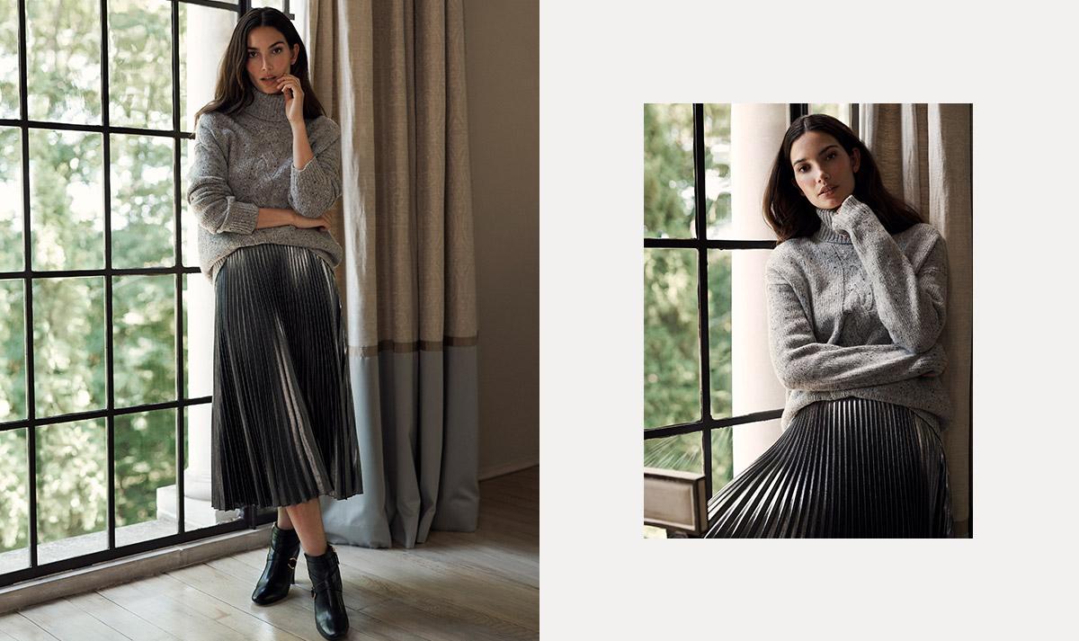 Woman wears grey turtleneck sweater and pleated metallic skirt.