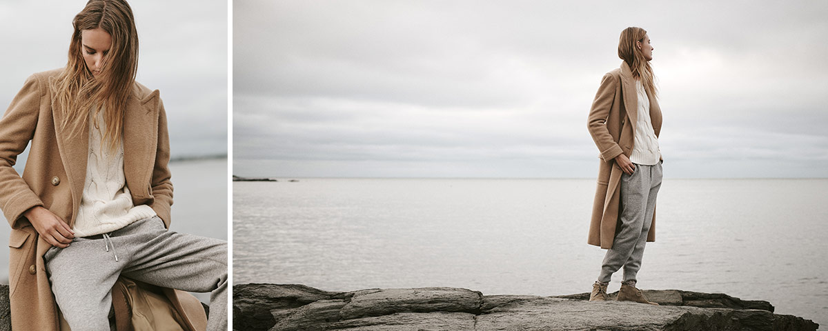 Woman in tan coat stands on rock by water