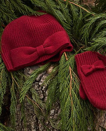 Red knit hat and mittens with bows on background of pine needles.