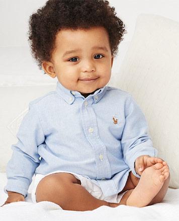Baby boy wears light blue button-down shirt.
