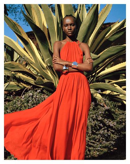 Woman in desert wears red halter-neck maxidress.