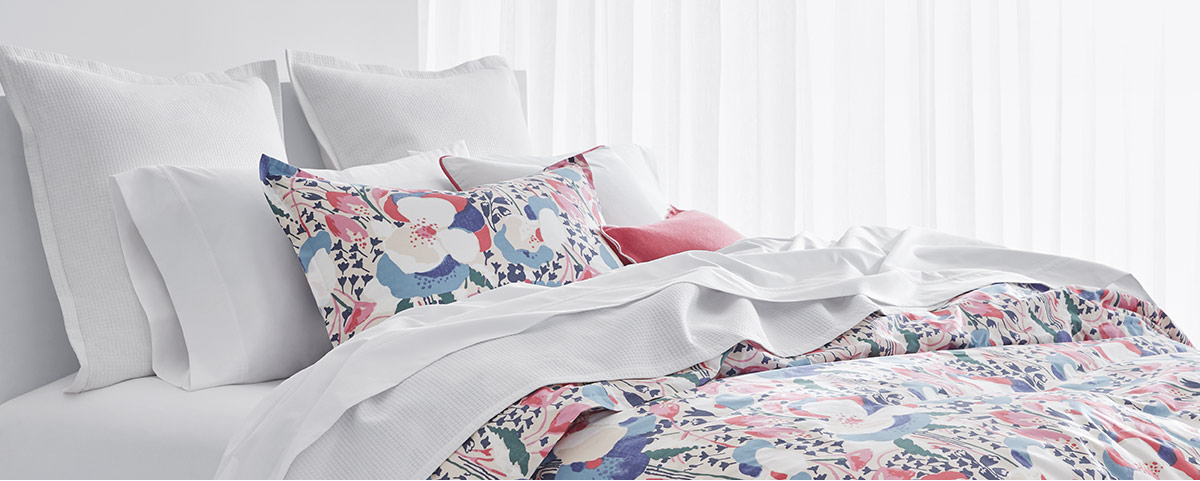 Bed with floral-print duvet in shades of blue & pink