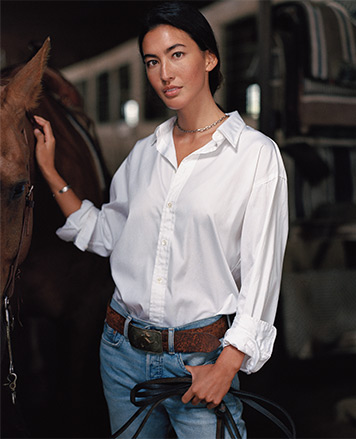 Woman in white blouse tucked into belted jeans