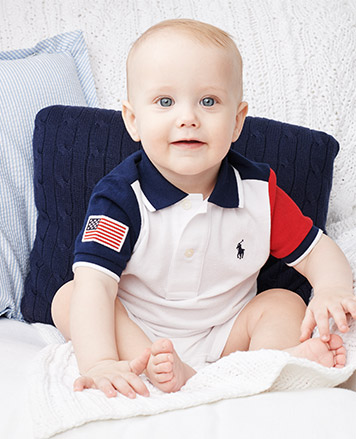 Baby boy wears color-blocked Polo shirt with American flag patch.