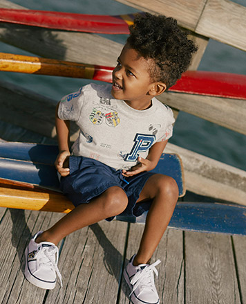Boy wears white T-shirt with varsity-inspired drawings all over.