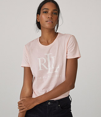 Woman wears light pink tee with monogram at chest.