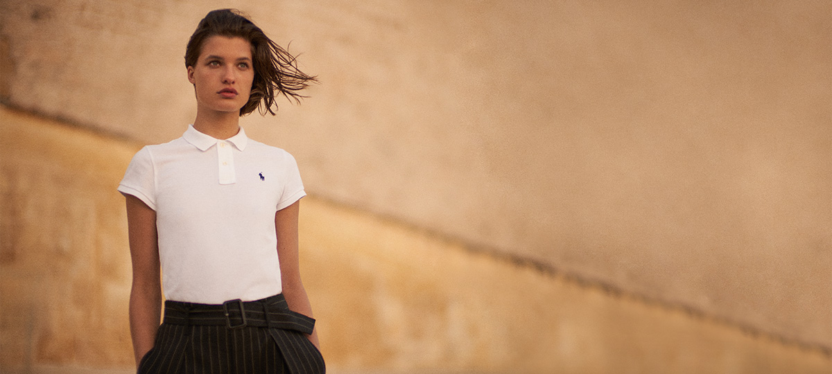 Woman in slim-fitting white Polo shirt paired with pinstripe pants