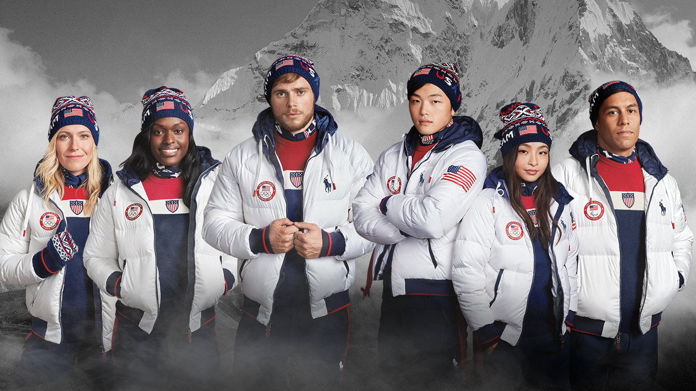 Team USA members against snowy mountain backdrop in closing ceremony uniform