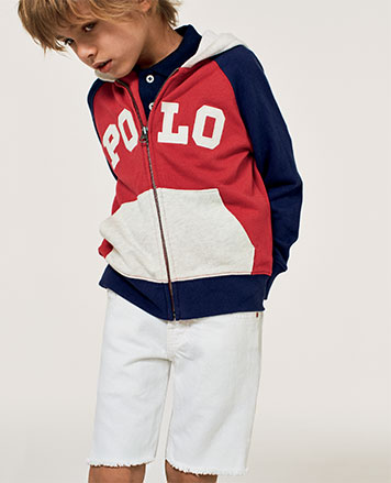 Boy wears white shorts with red, white, and blue hoodie.