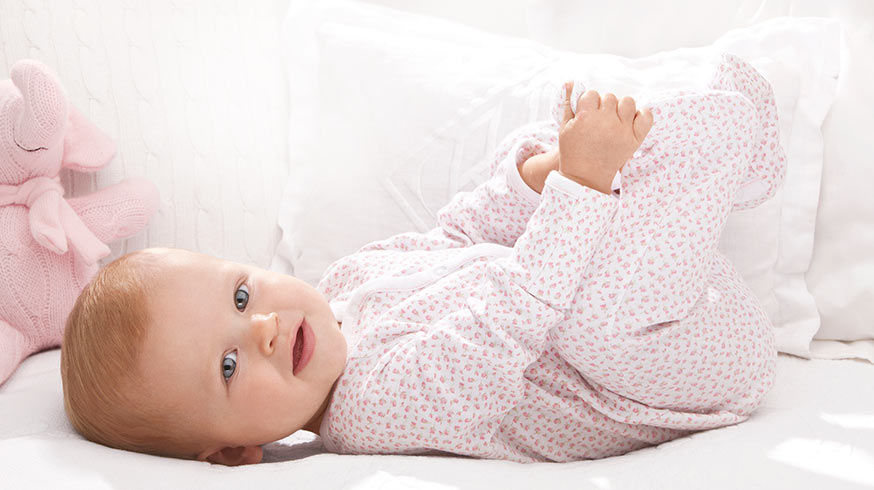 Baby in floral-print footed coverall plays with her feet