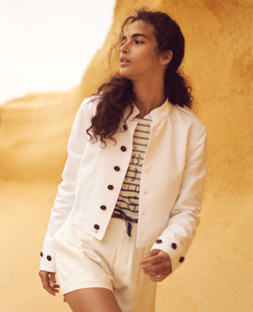 Woman in white cotton officer's jacket with start-embossed buttons