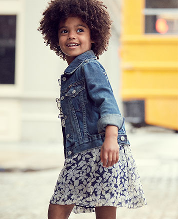 Girl wears floral dress and denim jacket.